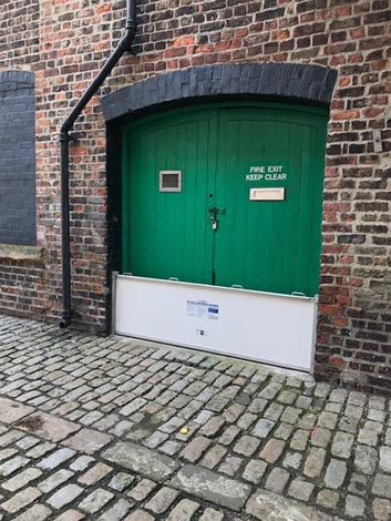 A business door with a flood gate set up in front