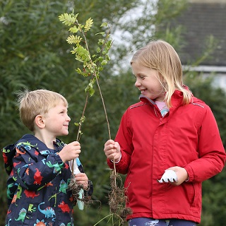 Two children carrying tree saplings ready to plant