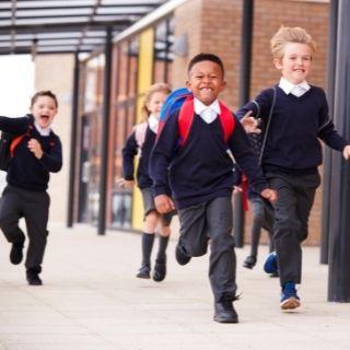 School children in uniform running on school grounds