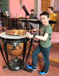 A young boy playing a large drum