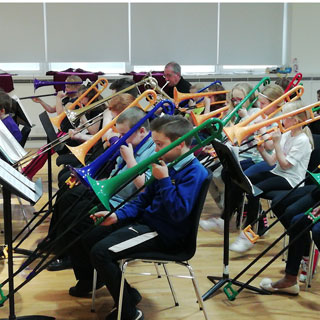 A group of kids playing with trombones