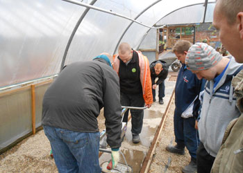 Gardeners fit a new bed in a greenhouse
