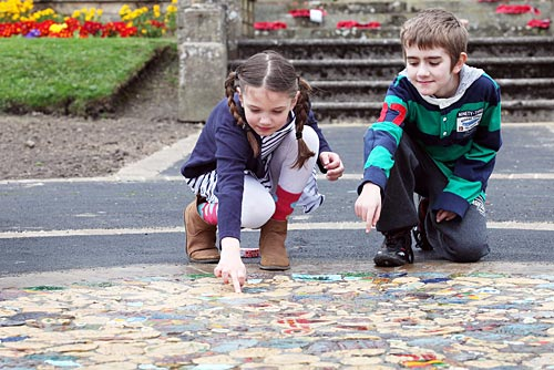 Two children looking at a mosaic
