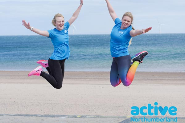 Two people jumping in the air with Active Northumberland t-shirts on