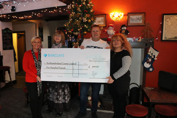 owners of the The Northumberland Arms handing over cheque.