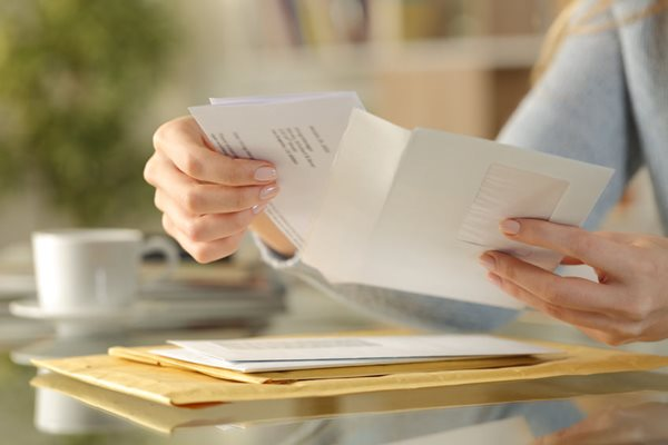 Photo of someone opening letter