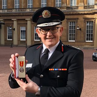Paul Hedley holding the Queen's Medal