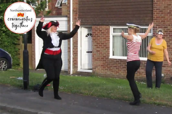 People dressed up dancing in their garden to Walking on Sunshine
