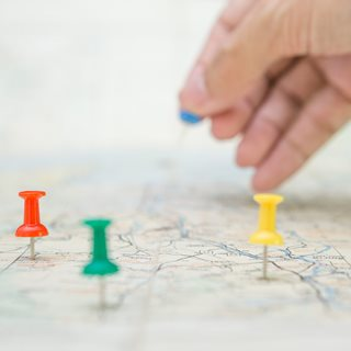Image of a map with coloured pins in it.