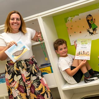 Cllr Caroline Ball, Ashington Central ward, presents Nathan Bush, 8, of Ashington with his Summer Reading Challenge prize