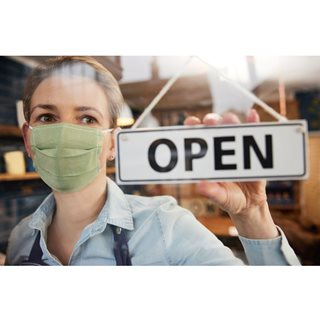 Photo of woman in mask turning Open sign