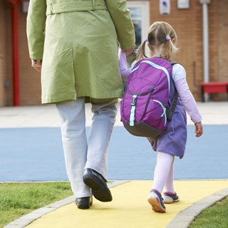 parent and young child walking into school