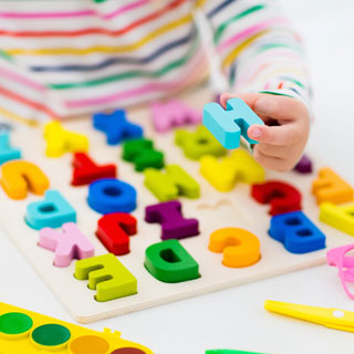 child learning alphabet with wooden letters