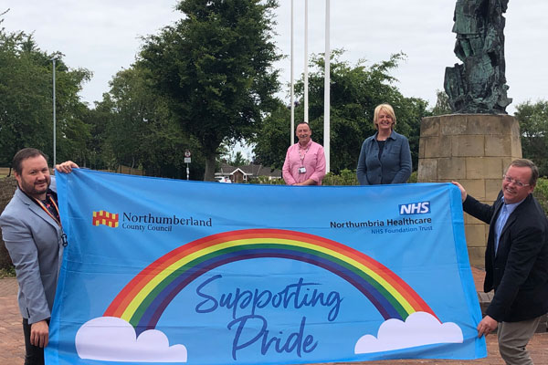 Cabinet members holding a Pride banner