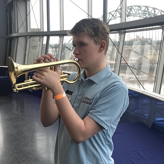 Ben, a teenage boy playing cornet with Tyne Bridge in background