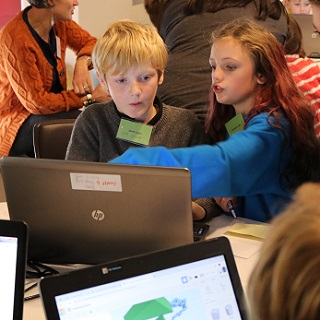 Two children are taught STEM subjects on a computer