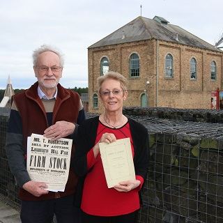 Dr Adrian Olser and Celia Collinson from the Alnmouth Local History Society standing outside of Woodhorn Museum with documents from Dickson, Archer and Thorp