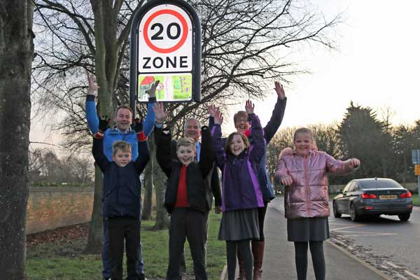 Children underneath a 20mph sign