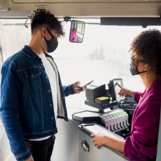 Young man paying for bus ticket wearing a mask
