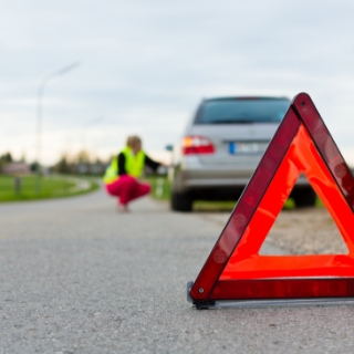 Neon orange triangle break down sign behind silver car at side of road