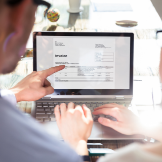 Laptop screen showing invoice and man pointing at the screen