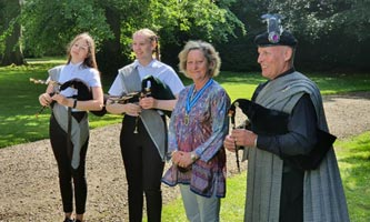 Richard Johnstone with students Tilly and Sophie standing next to the High Sheriff